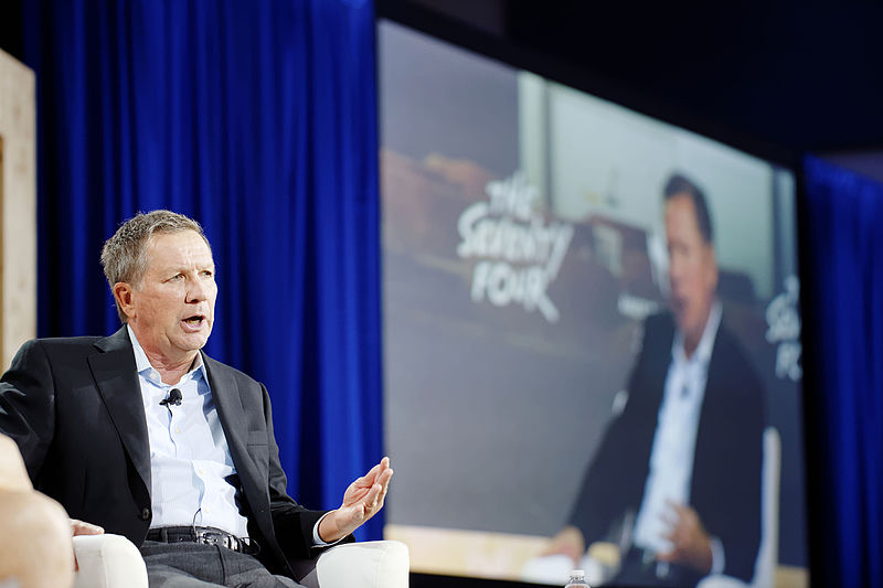 John Kasich sits speaking at a conference