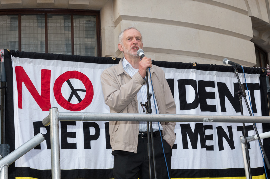 "Jeremy Corbyn giving a speech in front of a banner saying ""No Trident replacement"""
